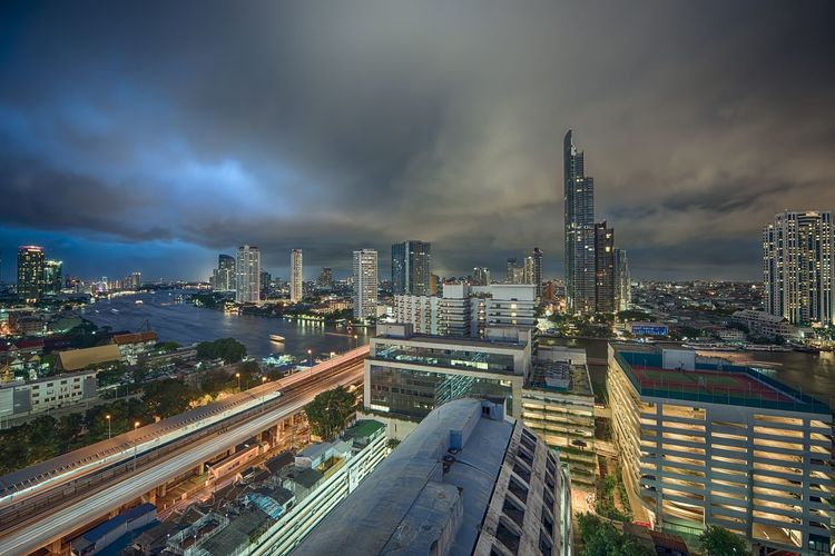 Modern illuminated buildings and chao phraya river against cloudy sky at dusk