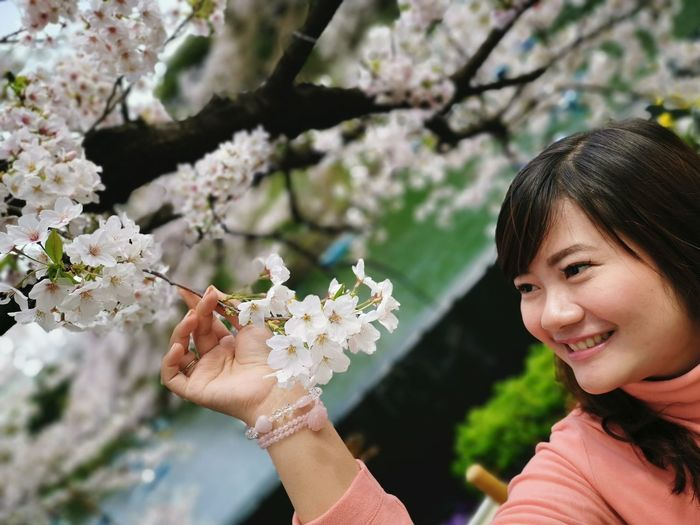 Portrait of smiling woman holding cherry blossom