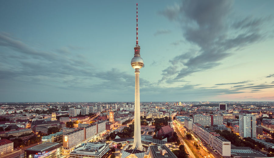 Television tower in illuminated city during sunset