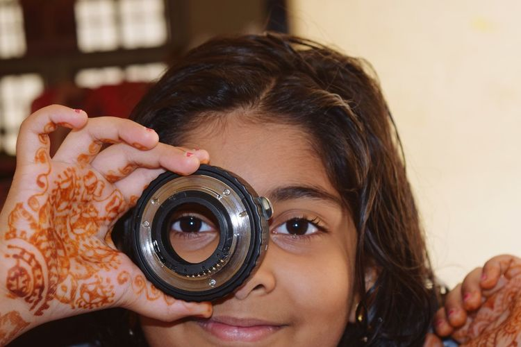 Close-up portrait of girl looking through lens