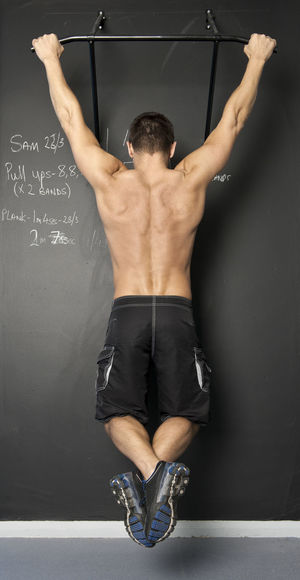 Rear view of shirtless man with arms raised against wall