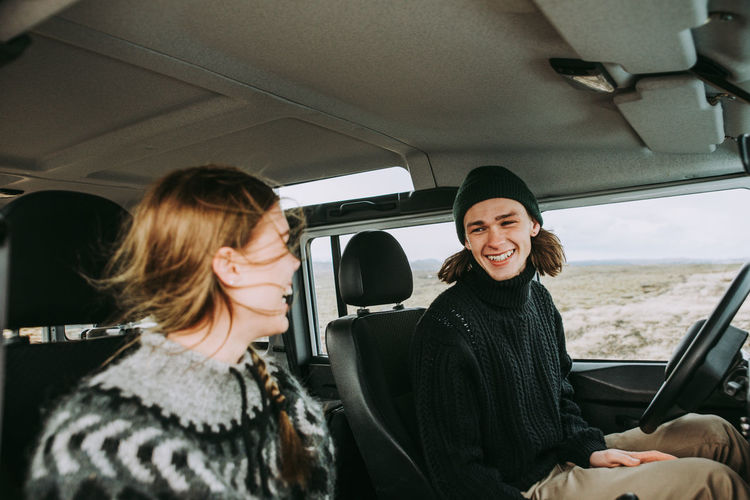 Smiling man and woman talking while sitting in car
