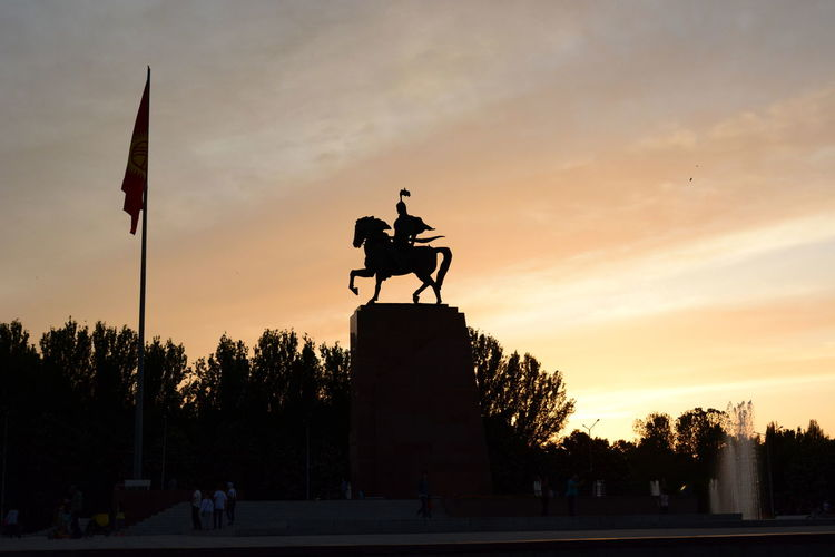 Manas monument silhouette at sunset. Ala Too square. Bishkek. Kyrgyzstan Outdoors Government Flag Memorial Orange Color Low Angle View History The Past Cloud - Sky Architecture Human Representation Nature Representation Statue Silhouette Sculpture Sunset Manas Bishkek Ala Too Square Kyrgyz Kyrgyzstan Central Asia Ex Soviet Countries Silk Road Monument Travel Destinations HERO Mythology Capital Cities