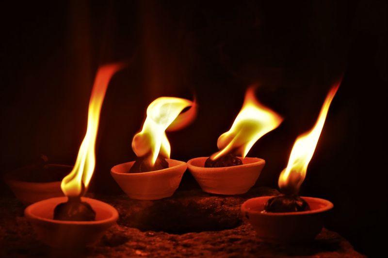 Close-Up Of Diyas Burning In Temple