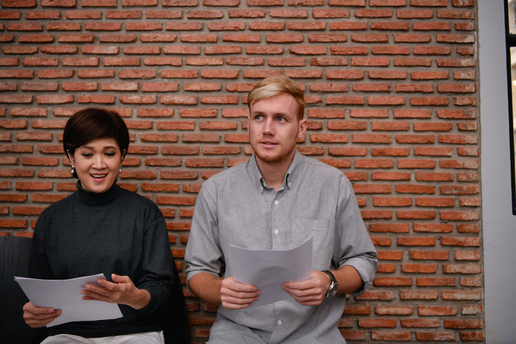 Candidates with resume sitting against brick wall in office