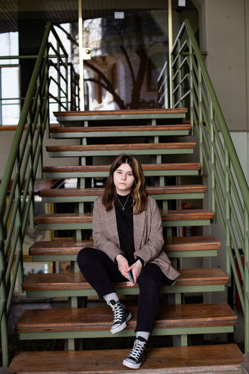 Portrait of young woman sitting on staircase