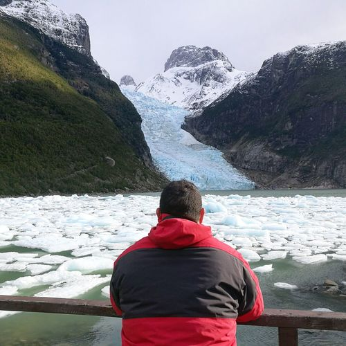 Rear view of man looking at snowcapped mountain