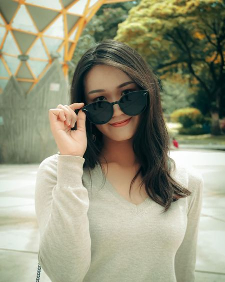 Portrait of beautiful young woman wearing sunglasses standing outdoors
