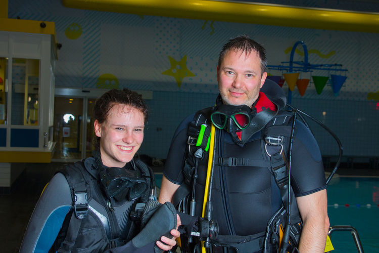 Portrait of smiling female scuba diver with instructor holding diving equipment
