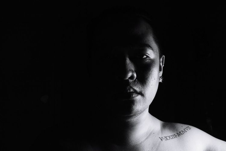 Portrait of shirtless man against black background