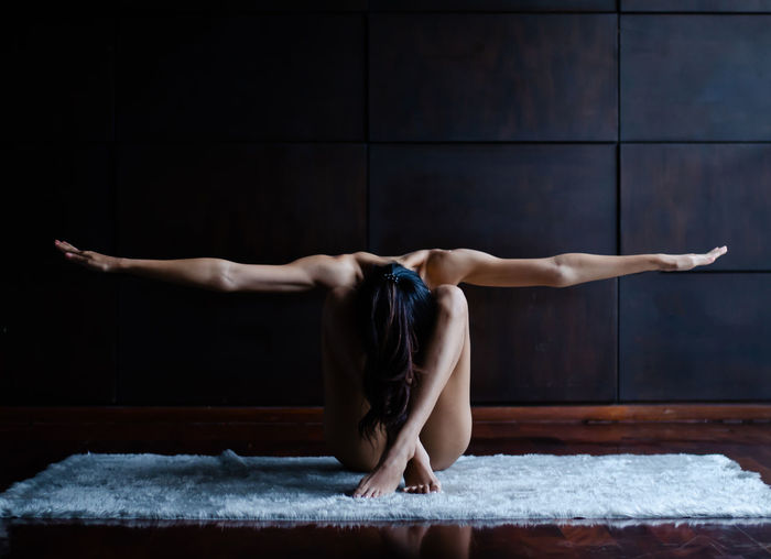 One Person Full Length Indoors  Healthy Lifestyle Exercising Balance Sport Adult Stretching Human Arm Limb Young Adult barefoot Elégance Strength Skill  Wellbeing Human Body Part Human Limb Flooring Arms Raised Beautiful Woman