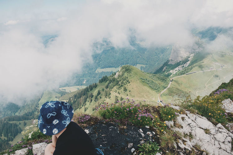 Woman wearing hat sitting at cliff against cloudy sky