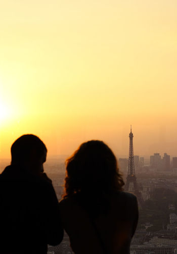 Rear view of people looking at cityscape during sunset