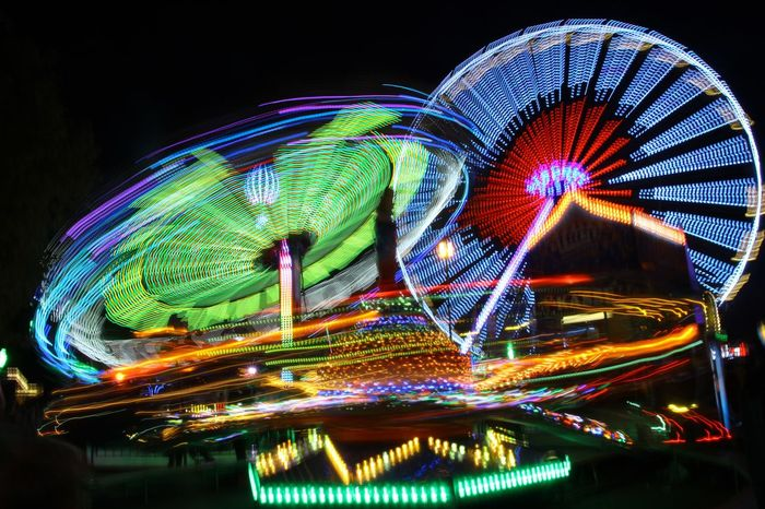 Amusement Park Ferris Wheel Night Arts Culture And Entertainment Illuminated Amusement Park Ride Multi Colored Long Exposure Light Trail Motion No People Clear Sky Sky Outdoors City Carousel City Focus On Foreground Close-up Connected By Travel My Best Travel Photo