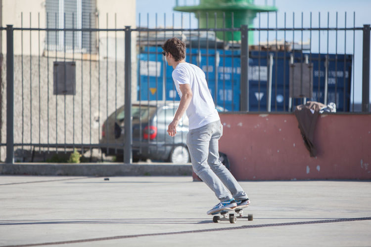 Young Man Skateboarding On Footpath On Sunny Day