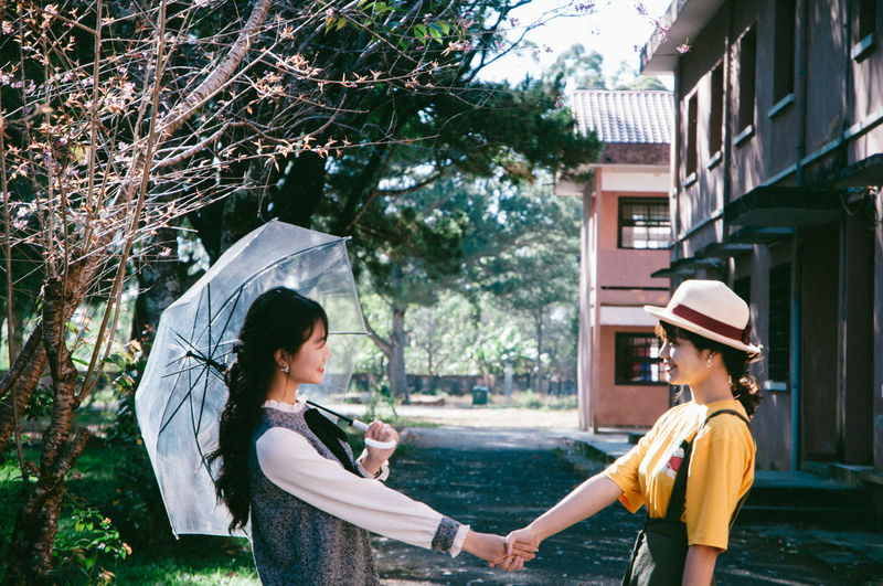 Friends shaking hands against houses and trees