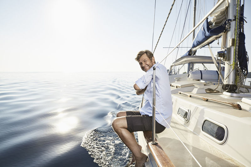 Man sitting on sailboat in sea against sky on sunny day