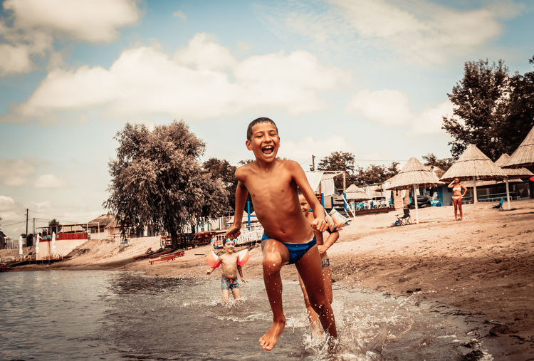Carefree boy running and having fun with friends on the beach in summer.
