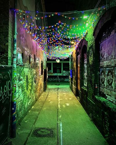 Illuminated footpath amidst buildings at night