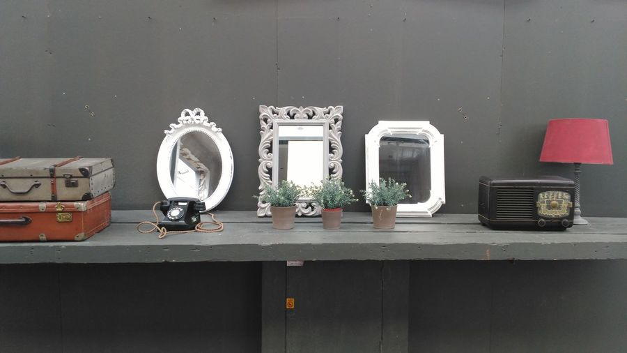 Various decoration and vintage electrical equipment on table by wall