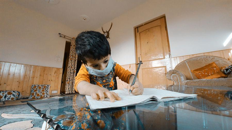 Boy wearing mask writing in book