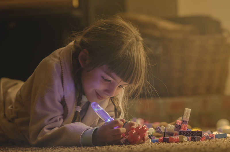 Smiling Girl Playing With Toys While Lying On Rug At Home
