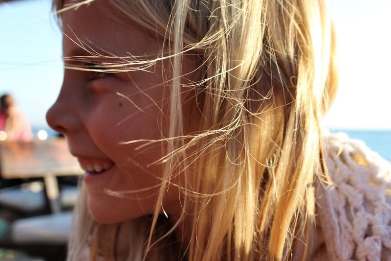Close-Up Of Girl With Tousled Hair Smiling Outdoors