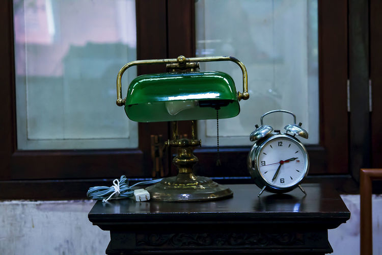 Close-up of clock on table against window