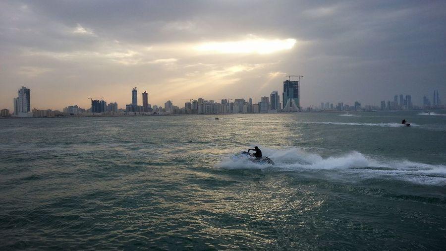 Jetskiing Manama Bahrain Cityscape Skyline Cloudy Skies Jetski Watersports People Leisure Activity Leisure Time Sunrays The Essence Of Summer Overcast Skies People And Places The City Light