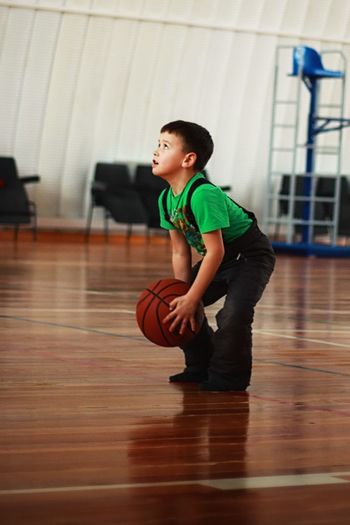 Boy playing with ball in court