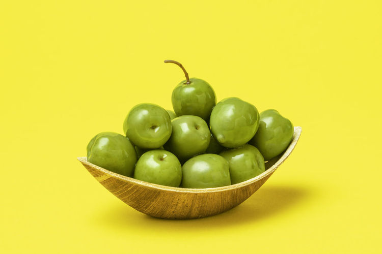 Green fruits in bowl against yellow background
