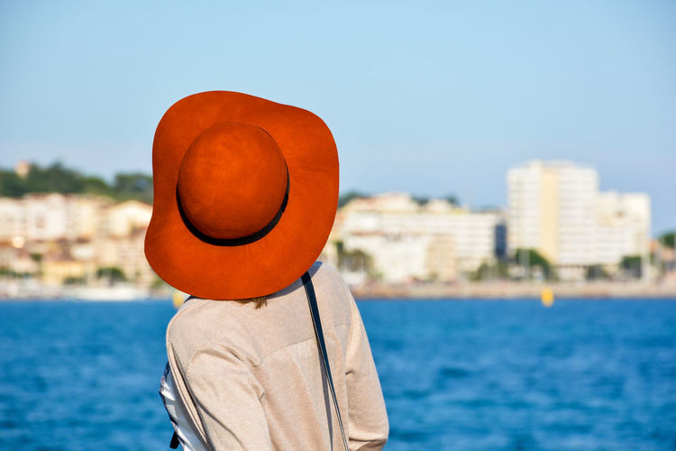 Rear view of woman in hat against river against sky