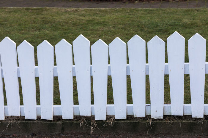 Asymmetrical Grass Painted Picket Fence Wood Barrier Board Carpentry Day Fence Field Garden Grass In A Row Lopsided Nature No People Outdoors Picket Plank Privacy Private Protection Uneven White