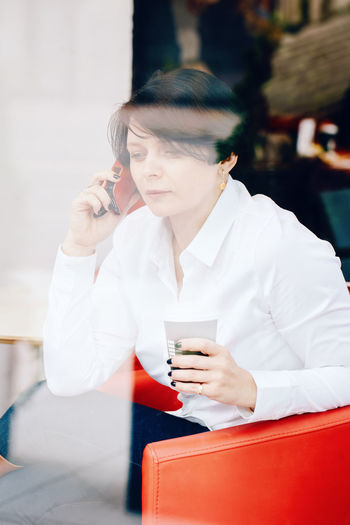 Woman talking over smart phone in cafe seen through window