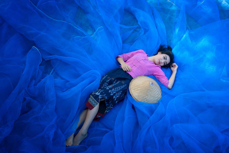 Beautiful Thai woman is harvesting indigo on blue net floor Beautiful Woman Bed Blue Day Eyes Closed  Full Length High Angle View Lifestyles Lying Down Lying On Back One Person One Young Woman Only People Portrait Real People Relaxation Sheet Sleeping Swimming Pool Water Young Adult Young Women