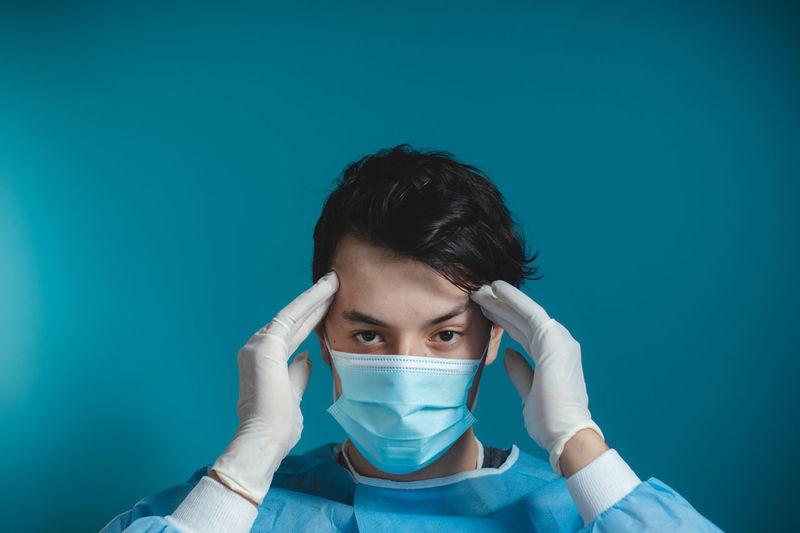 Portrait of teenage girl holding blue background
