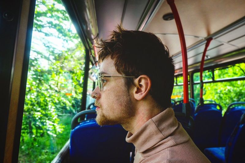 Side view of young man sitting in bus