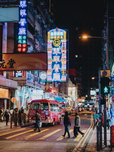 People walking on city street at night