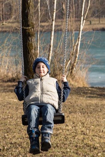 Portrait of boy swinging against lake during winter