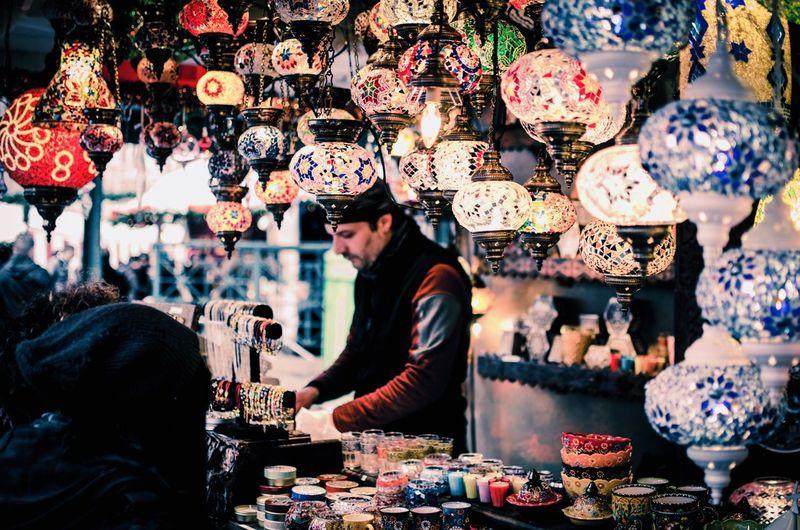 Man selling colorful lanterns at market