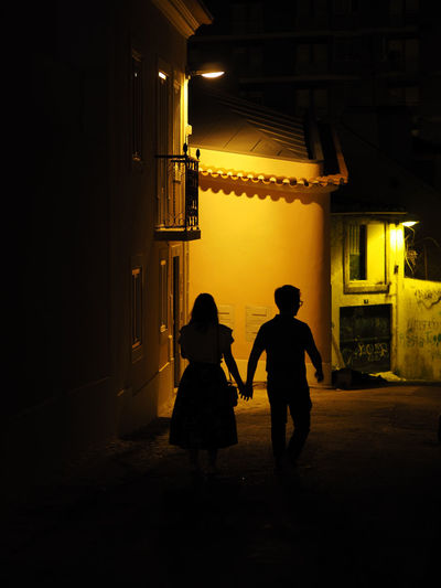 Two People Architecture Built Structure Real People Building Exterior Illuminated Building Walking Men Women Night Lifestyles Rear View Full Length People Silhouette Togetherness City Adult Leisure Activity Positive Emotion