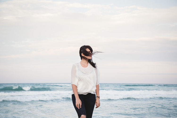 Portrait of a young beautiful woman with windy hair standing by the sea