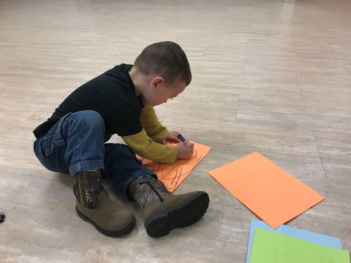 High angle view of boy drawing while sitting on floor