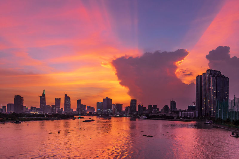 Scenic view of river amidst buildings against sky during sunset