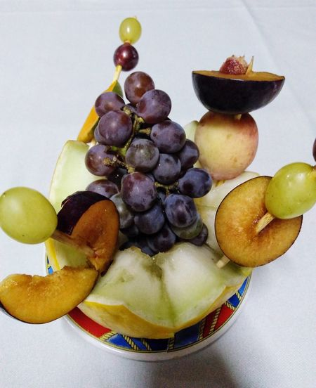 Close-up of grapes in plate against white background