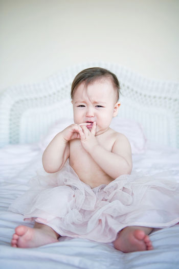 Full Length Portrait Of Cute Baby Girl Crying On Bed