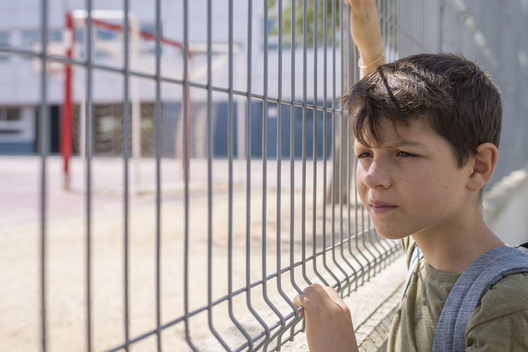 Boy standing by fence in schoolyard