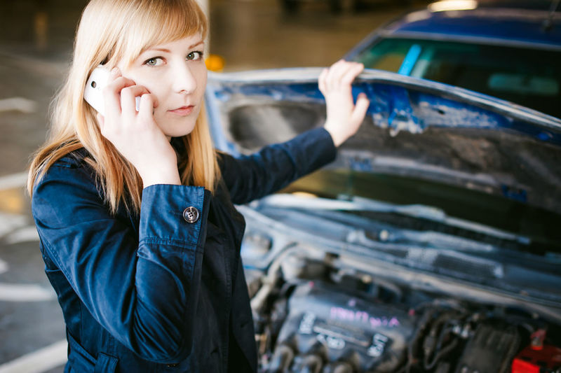 Portrait of woman talking on mobile phone by car
