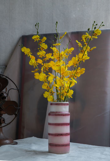 Yellow flower vase on table against wall at home