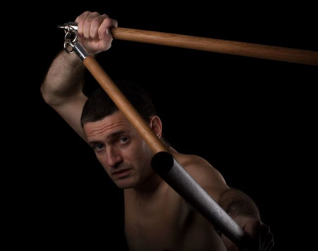 Portrait of shirtless man holding weapon against black background